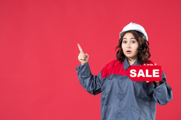 Draufsicht einer überraschten baumeisterin in uniform, die einen schutzhelm trägt und das verkaufssymbol auf der rechten seite auf isoliertem rotem hintergrund zeigt