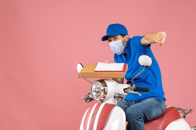 Draufsicht einer verrückten emotionalen männlichen lieferperson in maske mit hut, die auf einem roller sitzt und bestellungen mit dokument auf pfirsichhintergrund liefert