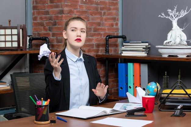 Draufsicht einer verwirrten frau, die an einem tisch sitzt und verpacktes papier im büro hält