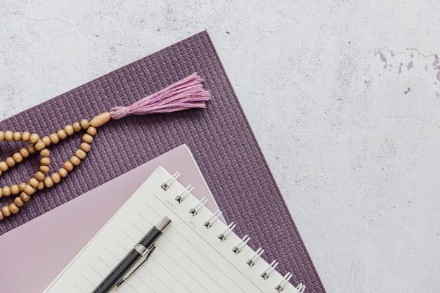 Draufsicht einer violetten yogamatte, schlechte holzperlen auf weißem hintergrund. unentbehrliches zubehör zum üben von yoga und meditation. speicherplatz kopieren