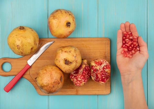Draufsicht einer weiblichen hand, die granatapfelkerne mit ganzen granatäpfeln auf einem hölzernen küchenbrett mit messer auf einer blauen oberfläche hält