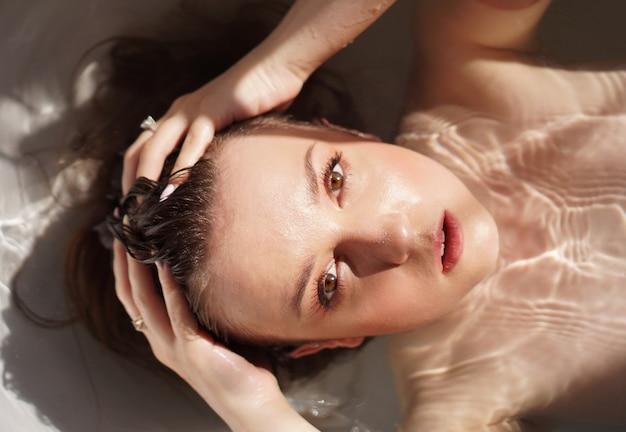 Draufsicht einer wunderschönen jungen frau, die ein bad nimmt und in die kamera schaut