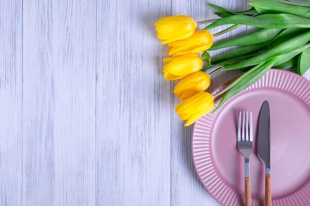Draufsicht einer zusammensetzung eines straußes der gelben tulpen, einer rosa platte mit besteck auf einem hellen holzhintergrund.
