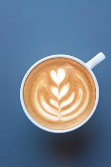 Draufsicht eines bechers latte art auf dunklem hintergrund