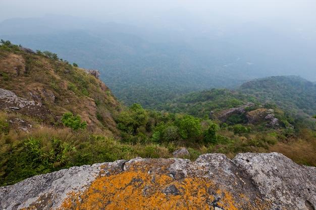 Draufsicht eines berges. klaffende raumklippe mit berg auf blauem himmel der wolken und dem wald