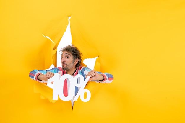 Draufsicht eines ehrgeizigen bärtigen mannes, der zehn prozent in einem zerrissenen loch in gelbem papier zeigt