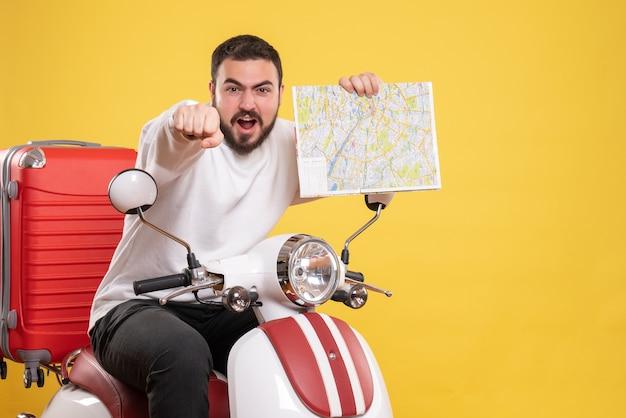 Draufsicht eines ehrgeizigen jungen mannes, der auf einem motorrad mit koffer darauf sitzt und karte auf isoliertem gelbem hintergrund hält