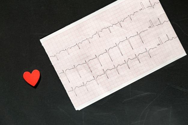 Draufsicht eines elektrokardiogramms in papierform mit rotem hölzernem herzen. ekg- oder ekg-papier auf schwarz. medizin- und gesundheitskonzept.