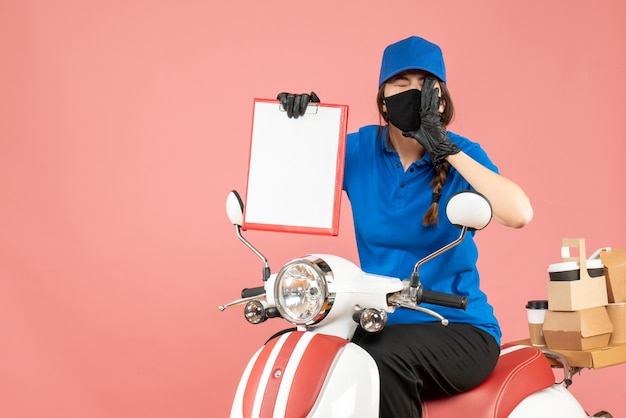 Draufsicht eines emotionalen kuriermädchens mit medizinischer maske und handschuhen, das auf einem roller sitzt und ein leeres papierblatt hält, das bestellungen auf pastellfarbenem pfirsichhintergrund liefert
