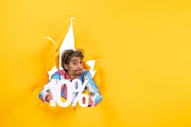 Draufsicht eines enttäuschten bärtigen mannes, der zehn prozent in einem zerrissenen loch in gelbem papier zeigt