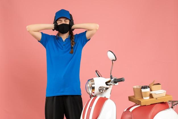 Draufsicht eines erschöpften kuriermädchens in medizinischer maske, das neben dem motorrad mit kaffeekuchen auf pastellfarbenem hintergrund steht