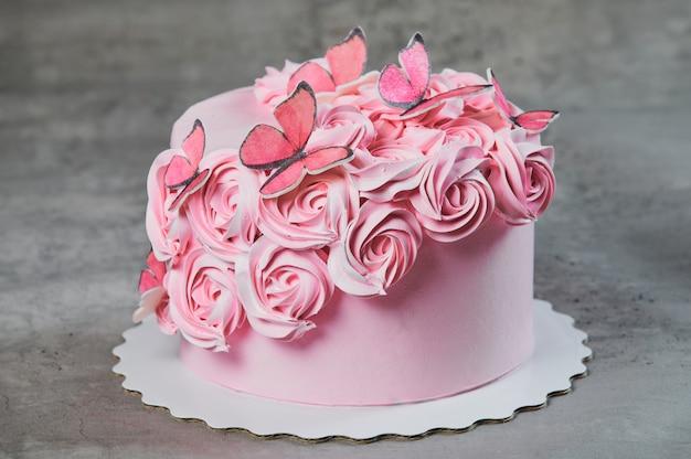 Draufsicht eines frisch gebackenen kuchens verziert mit rosa puderzuckerrosen, die auf einem kuchenstand über einem schwarzen hintergrund mit copyspace angezeigt werden.