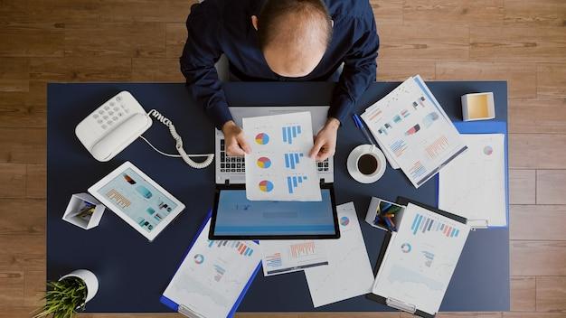 Draufsicht eines geschäftsmannes, der managementdiagramme analysiert, dokumentiert brainstorming-strategieideen des unternehmens