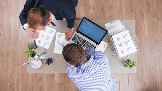Draufsicht eines geschäftsmannes, der managementdiagramme analysiert und die unternehmensstrategie diskutiert
