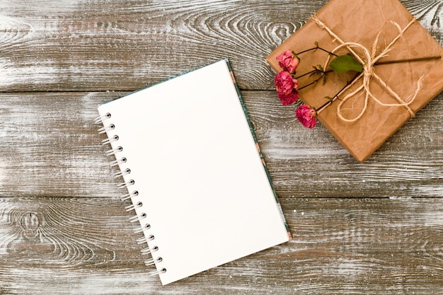 Draufsicht eines geschenks eingewickelt im kraftpapier und in einem tagebuch oder in einem notizbuch und in einer getrockneten rosafarbenen blume auf einem grauen holztisch. flaches design. kopieren sie platz