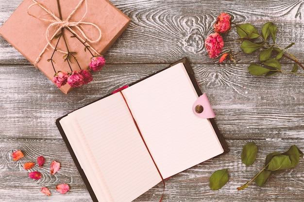 Draufsicht eines geschenks eingewickelt im kraftpapier und in einem tagebuch oder in einem notizbuch und in einer getrockneten rosafarbenen blume auf einem grauen holztisch. flaches design.