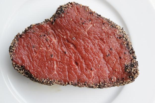 Draufsicht eines gewürzten rohen steaks auf einem teller auf dem tisch
