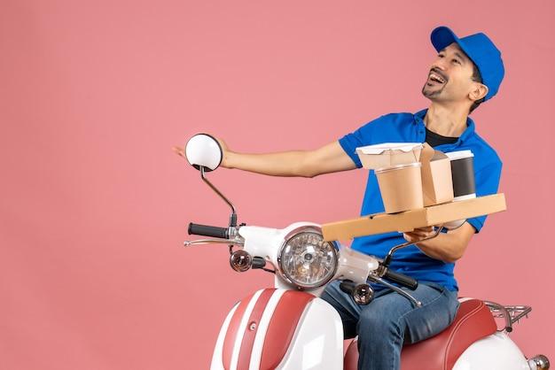 Draufsicht eines glücklichen emotionalen kuriermannes mit hut, der auf einem roller auf pastellfarbenem pfirsichhintergrund sitzt
