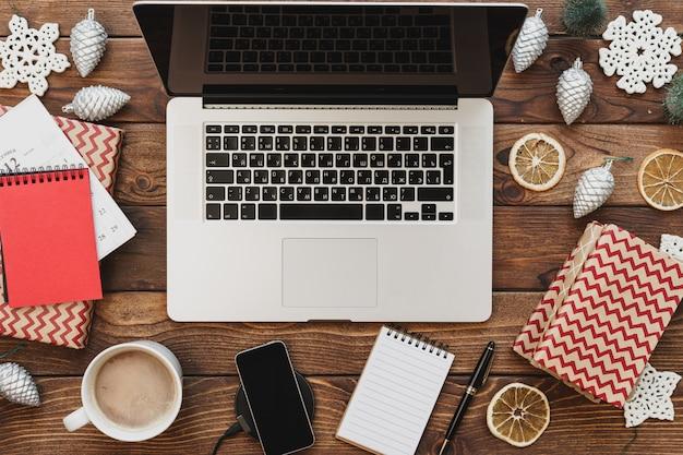 Draufsicht eines hölzernen desktops mit computer mit büroartikel und weihnachtsdekorationen