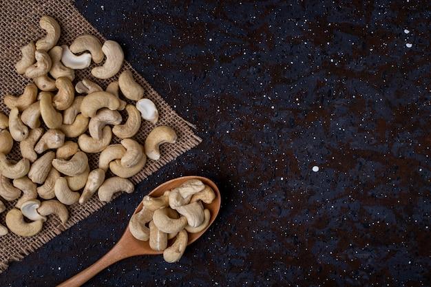 Draufsicht eines hölzernen löffels mit cashew auf schwarzem hintergrund mit kopienraum