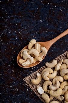 Draufsicht eines hölzernen löffels mit cashew auf schwarzem hintergrund