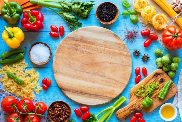 Draufsicht eines holztischs voll italienischer teigwaren ingradients mögen pfeffer, tomaten, olivenöl, basi