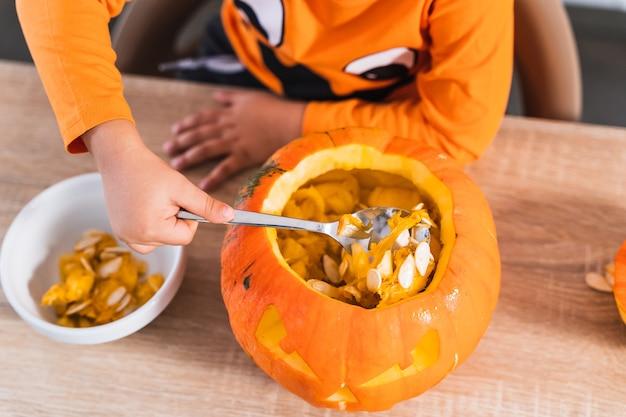 Draufsicht eines jungen, der als halloween-kürbis gekleidet ist und einen kürbis leert, um ihn für halloween zu dekorieren