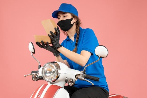 Draufsicht eines jungen fokussierten weiblichen kuriers mit medizinischer maske und handschuhen, der die schachtel auf pastellpfirsich öffnet