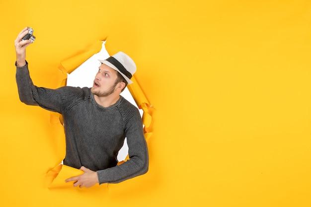 Draufsicht eines jungen mannes mit einem hut, der die kamera in einer zerrissenen gelben wand hält und betrachtet