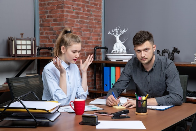 Draufsicht eines jungen motivierten und fleißigen büroteams, das sich auf ein thema in der büroumgebung konzentriert