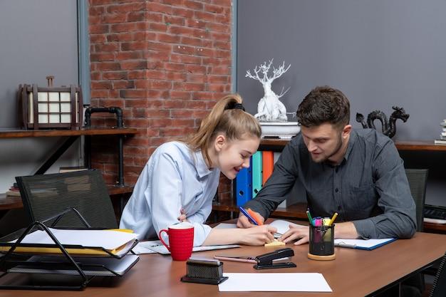 Draufsicht eines jungen motivierten und glücklichen hart arbeitenden büroteams, das sich auf ein thema in der büroumgebung konzentriert