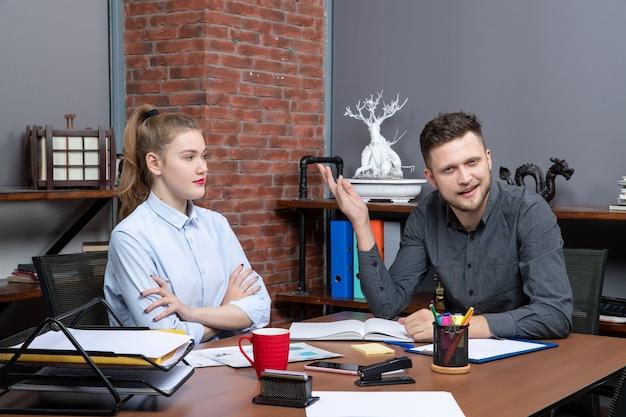 Draufsicht eines jungen neugierigen büroteams, das am tisch sitzt und ein wichtiges thema im büro diskutiert