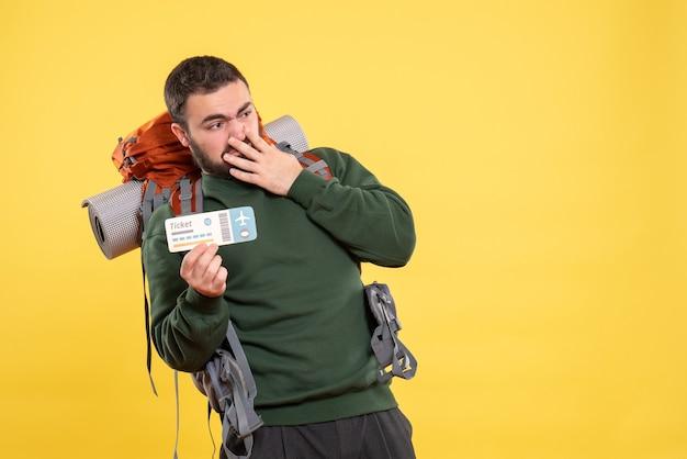 Draufsicht eines jungen überraschten reisenden kerls mit rucksack und zeigt das gefühl, das ticket verwirrt auf gelb