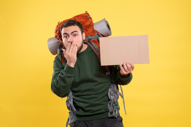 Draufsicht eines jungen verwirrten reisenden kerls mit rucksack, der ein blatt hält, ohne auf gelb zu schreiben