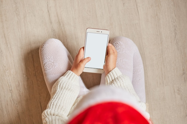 Draufsicht eines kleinen mädchens, das mit einem smartphone auf dem boden sitzt, ein handy mit leerem bildschirm für werbung oder werbung hält, weiße kleidung und roten hut trägt.
