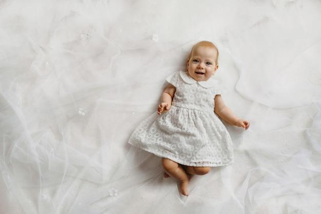 Draufsicht eines kleinen mädchens mit aufrichtigem lächeln, das auf dem rücken auf weißem bettlaken liegt, in weißem kleid gekleidet ist und geradeaus schaut