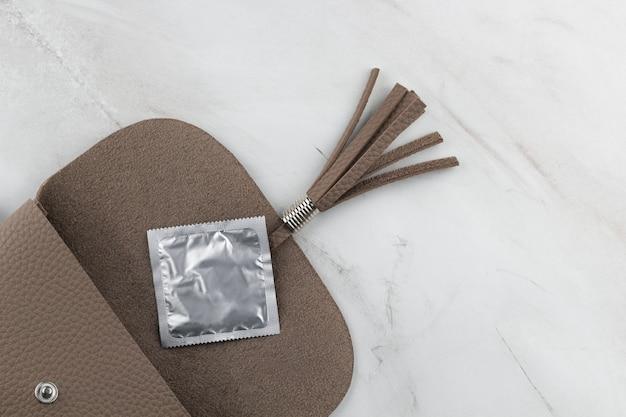 Draufsicht eines kondoms in einer offenen tasche auf der marmortabelle