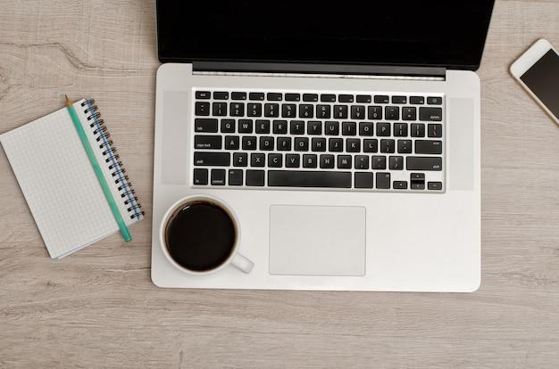 Draufsicht eines laptops, des smartphones, des notizbuches mit einem bleistift und eines tasse kaffees