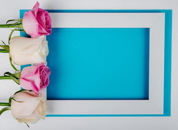 Draufsicht eines leeren bilderrahmens mit weißen und rosa rosen auf blauem hintergrund mit kopienraum