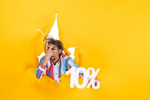 Draufsicht eines lustigen jungen mannes, der zehn prozent in einem zerrissenen loch in gelbem papier zeigt