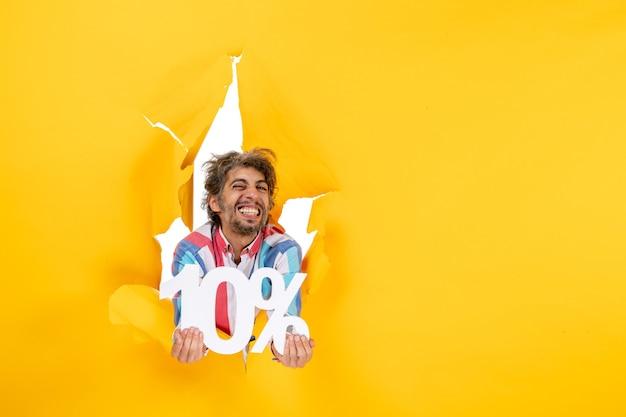 Draufsicht eines lustigen und emotionalen bärtigen mannes, der zehn prozent in einem zerrissenen loch in gelbem papier zeigt