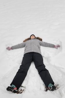 Draufsicht eines mädchens, das im schnee trägt warme kleidung spielt