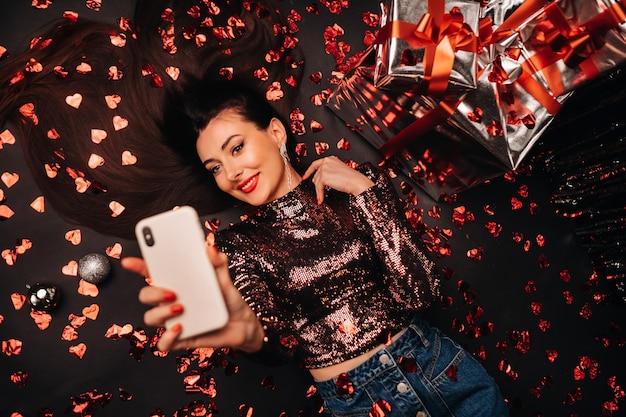 Draufsicht eines mädchens, das in glänzenden kleidern auf dem boden in konfetti in form von herzen liegt und ein selfie nimmt.