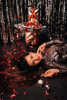 Draufsicht eines mädchens, das in glänzenden kleidern auf dem boden in konfetti in form von herzen und geschenken liegt.