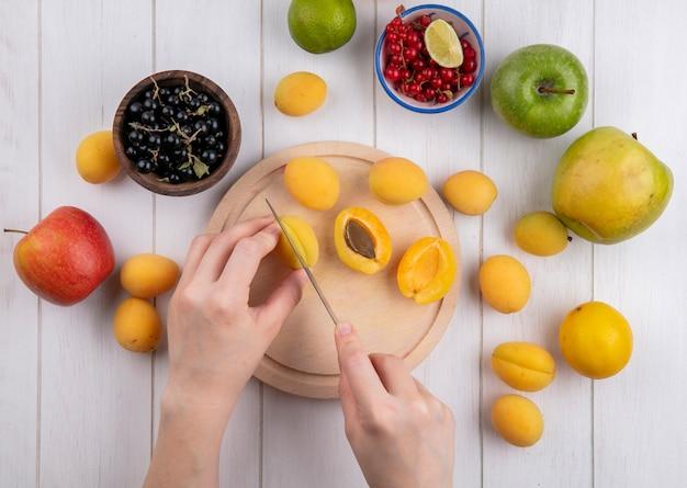 Draufsicht eines mädchens schneidet aprikosen auf einem ständer mit äpfeln und schwarzen und roten johannisbeeren auf einer weißen oberfläche