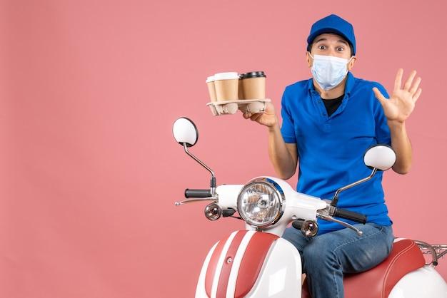 Draufsicht eines männlichen lieferers in maske mit hut, der auf einem roller sitzt und bestellungen liefert, die sich auf pfirsichhintergrund schockiert fühlen