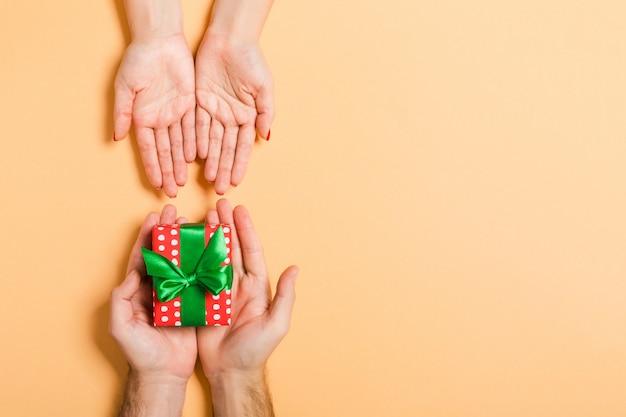 Draufsicht eines mannes, der einer frau ein geschenk hält und gibt. ein geschenk erhalten. abschluss oben des feiertagskonzeptes