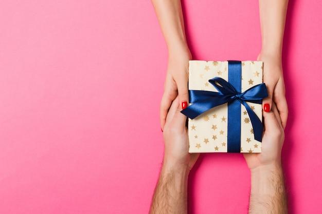 Draufsicht eines mannes und der frau, die ein geschenk auf buntem hintergrund halten