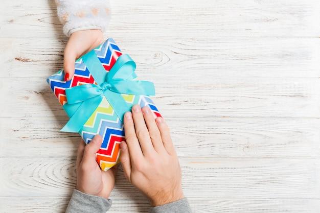 Draufsicht eines mannes und der frau, die ein geschenk halten. konzept des gebens und des empfangens eines geschenks mit kopienraum