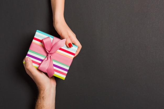 Draufsicht eines mannes und der frau, die eine geschenkbox auf buntem hintergrund halten